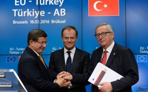 (From L) Turkish Prime Minister Ahmet Davutoglu, European Union Council President Donald Tusk and European Union Commission President Jean-Claude Juncker shake hands at the end of an European Union Summit held at the EU Council building in Brussels, on March 18, 2016. EU leaders and Turkey's prime minister approved a controversial deal to curb the huge flow of asylum seekers to Europe, with all migrants arriving in Greece from Sunday to be sent back. / AFP PHOTO / THIERRY CHARLIERTHIERRY CHARLIER/AFP/Getty Images