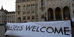 Activists hold up a banner with 'Refugees welcome' as sympathizers of several civil organizations protest against the migration policy of the Orban government in front of the parliament building in Budapest on September 30, 2016. A referendum on the European Union's migrant resettlement plans will be held on Sunday  in Hungary.   / AFP / ATTILA KISBENEDEK        (Photo credit should read ATTILA KISBENEDEK/AFP/Getty Images)